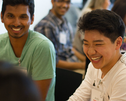 Students smiling while sitting at a table